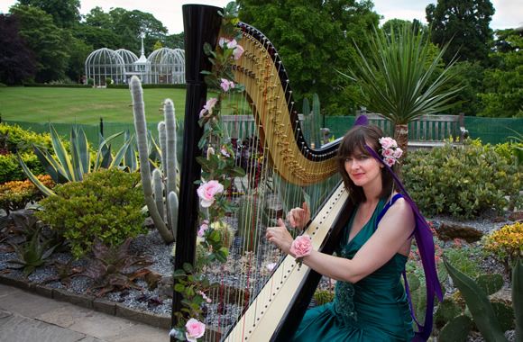 Ruby Paul Harpist garlanded with flowers at Birmingham Botanical Gardens